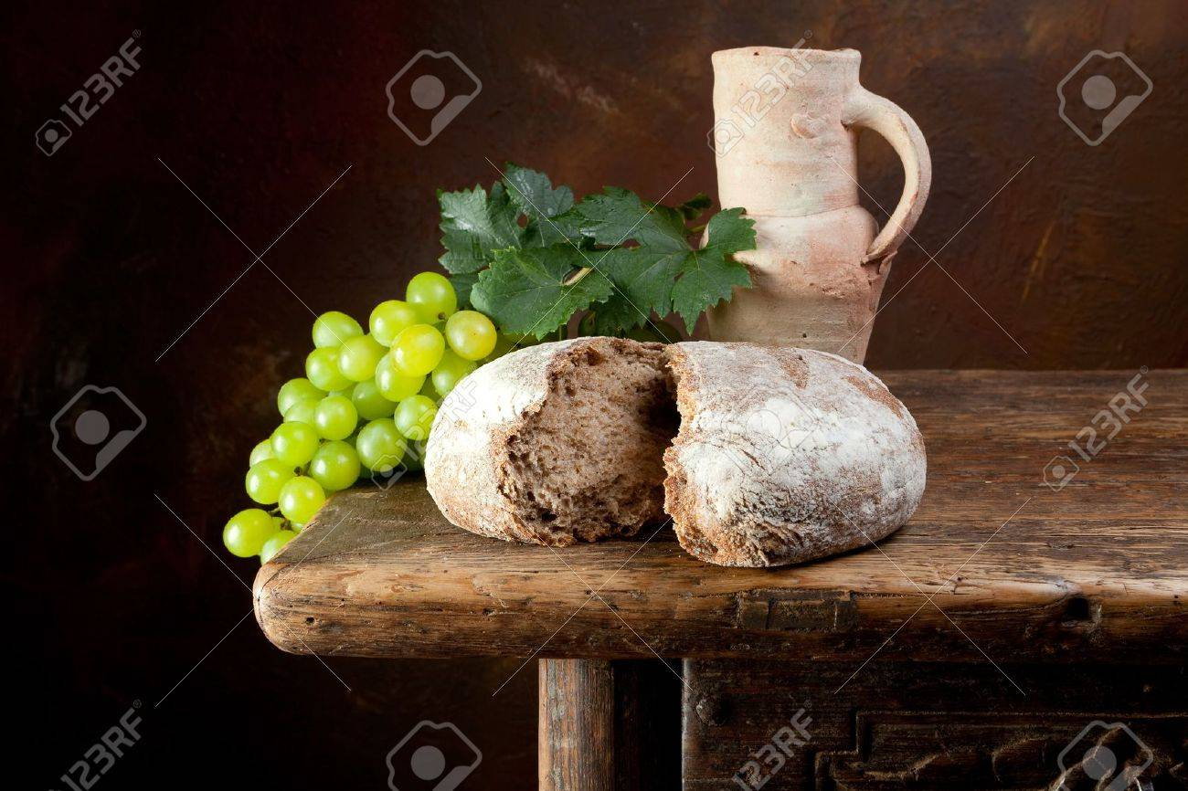 Antique wine jug with grapes and holy bread Stock Photo - 8835998