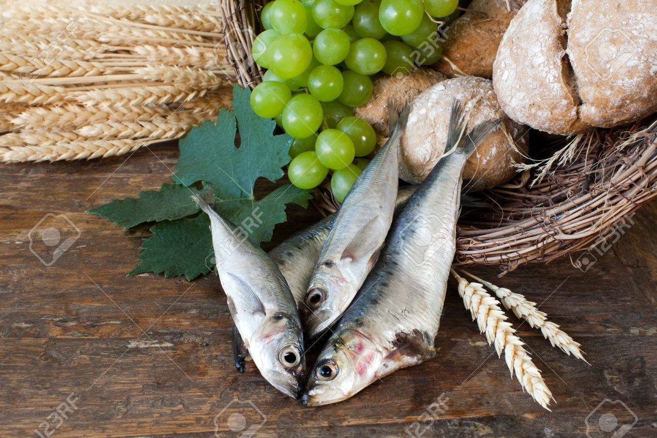 Bread and fish with wine grapes symbolizing the miracles of Jesus Christ Stock Photo - 9279319