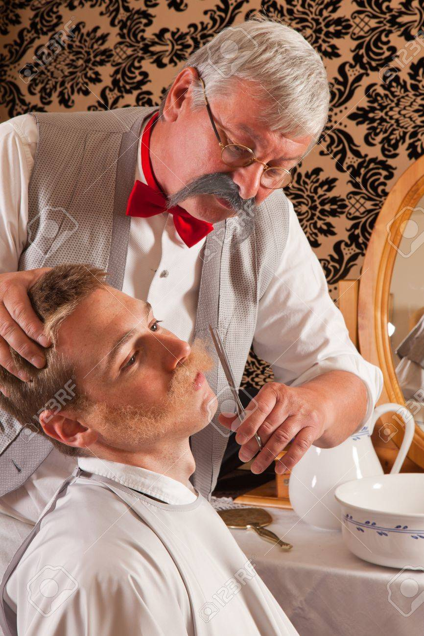 Barber cutting the mustache of a customer in an antique victorian barbershop Stock Photo - 9600586