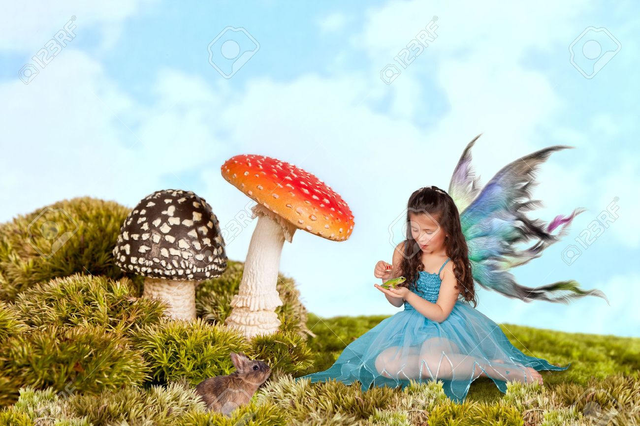 Little fairy girl with wings putting a crown on a green tree frog Stock Photo - 9684090