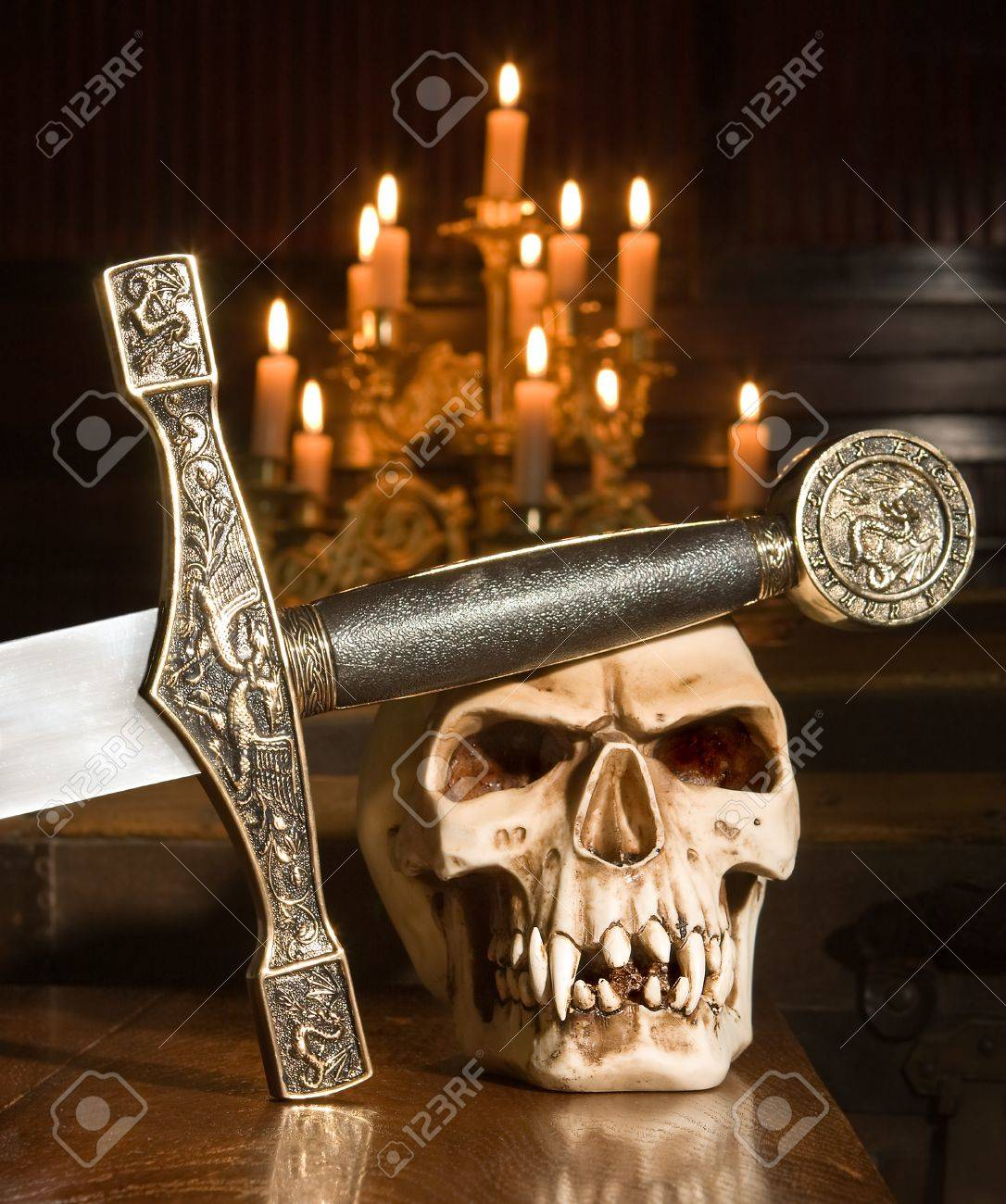 Medieval sword and skull lit by candles Stock Photo - 10480448