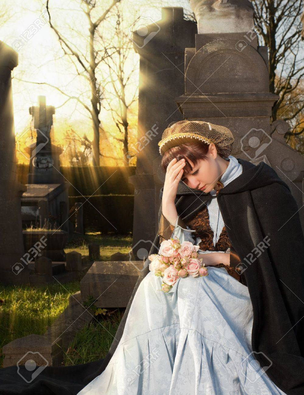 young victorian widow mourning on a tombstone at halloween stock