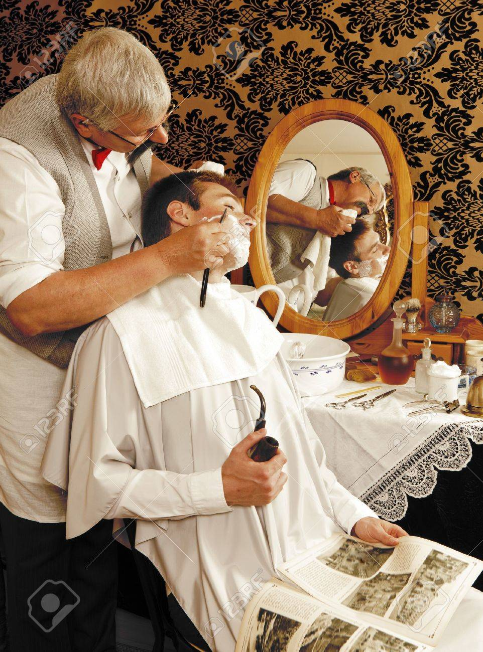 Victorian barber shaving a customer (the antique magazine is from 1910). Stock Photo - 10554617