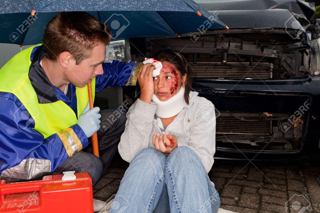 Paramedic caring for an injured woman under an umbrella - 10619945