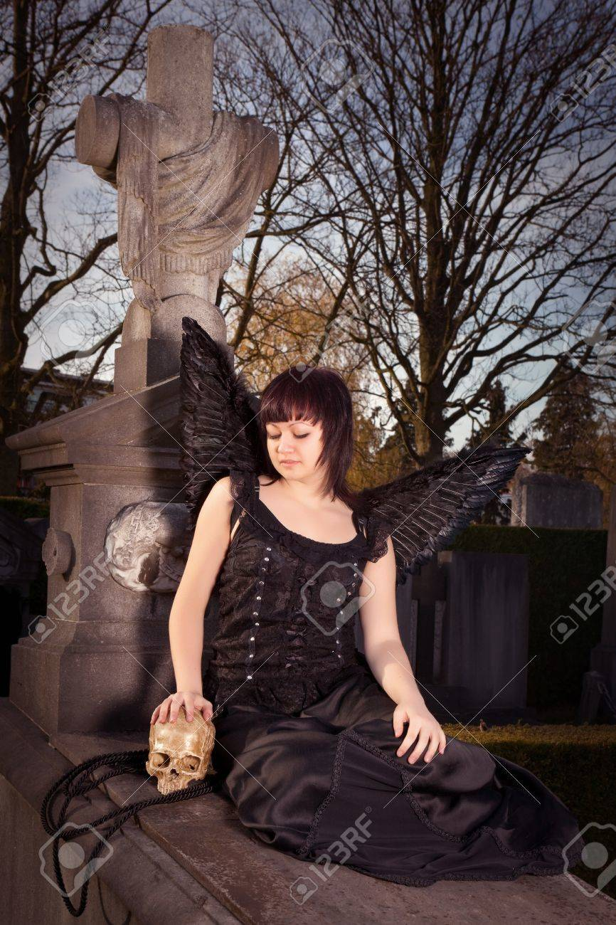 Gothic girl with black angel wings holding a skull on a tombstone Stock Photo - 10619935