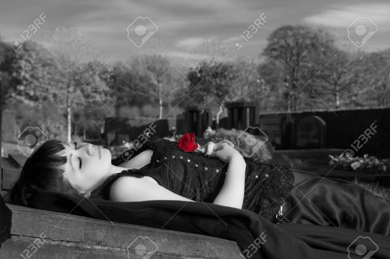 Gothic widow lying on a tombstone with a red rose Stock Photo - 10761414