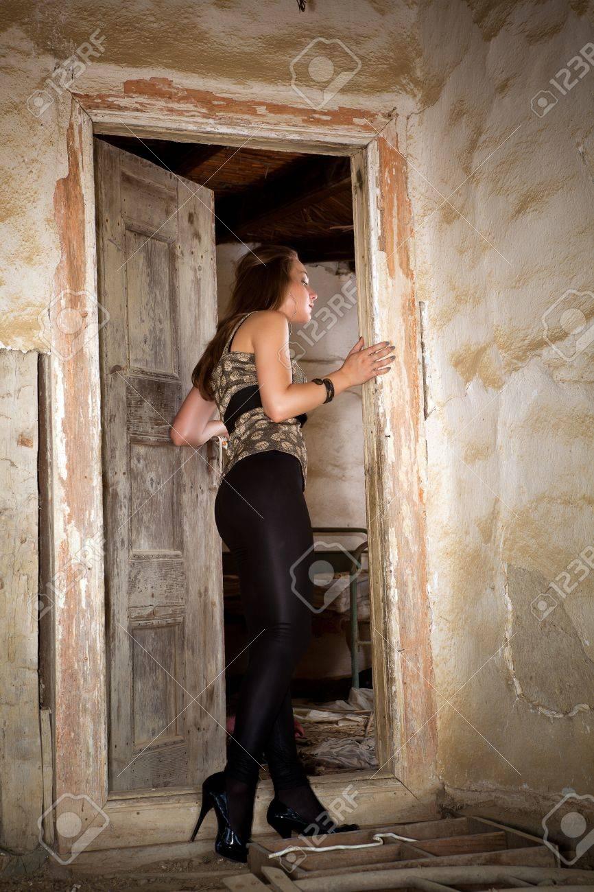 Modern young woman entering a derelict house Stock Photo - 13963602