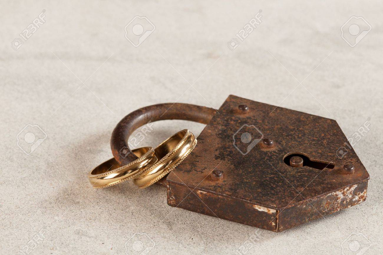 stock photo wedding rings locked up by a rusty old padlock - Old Wedding Rings