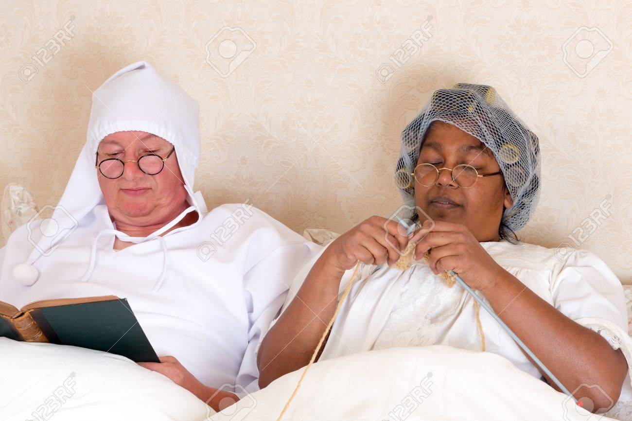 Retired couple reading and knitting in bed in vintage clothing Stock Photo - 15692670