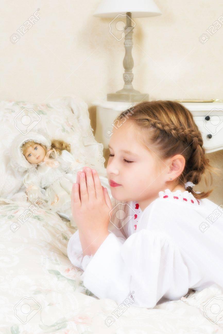 Vintage petite fille en disant ses prières dans sa chambre, à côté de sa  poupée antique