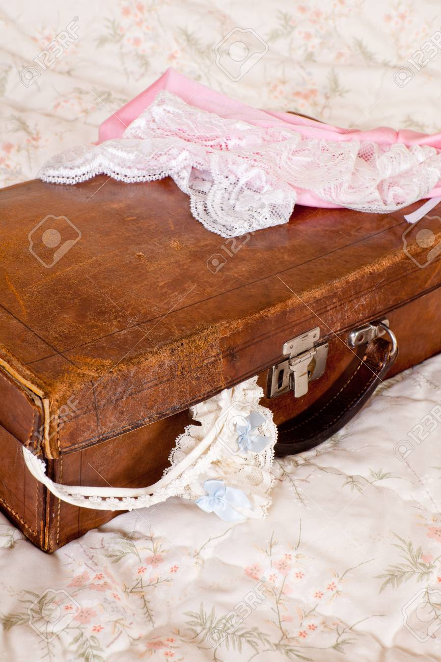 Bed with vintage leather suitcase and sexy bridal lingerie Stock Photo - 17218713