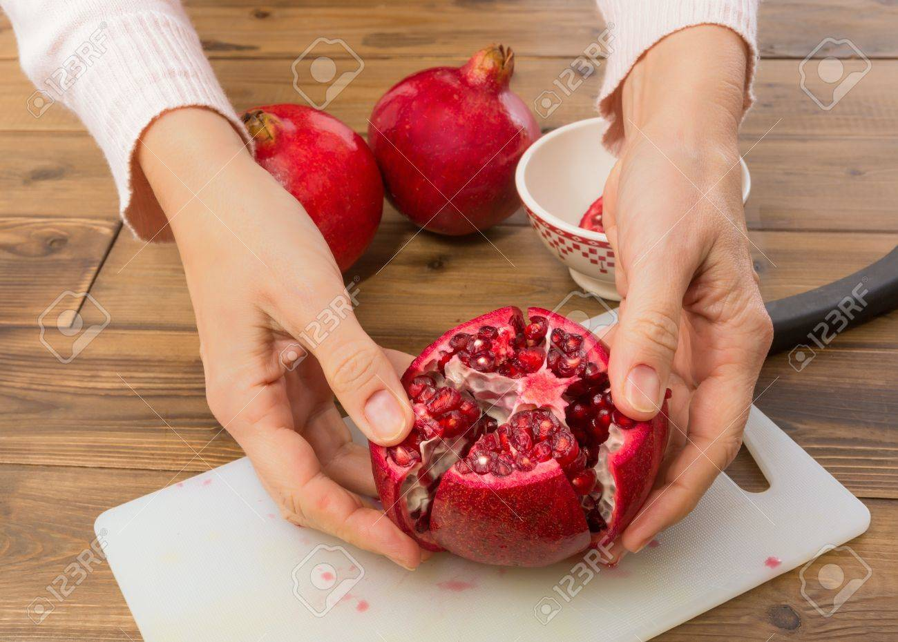 Hands opening a pomegranate and showing the seeds Stock Photo - 17779416