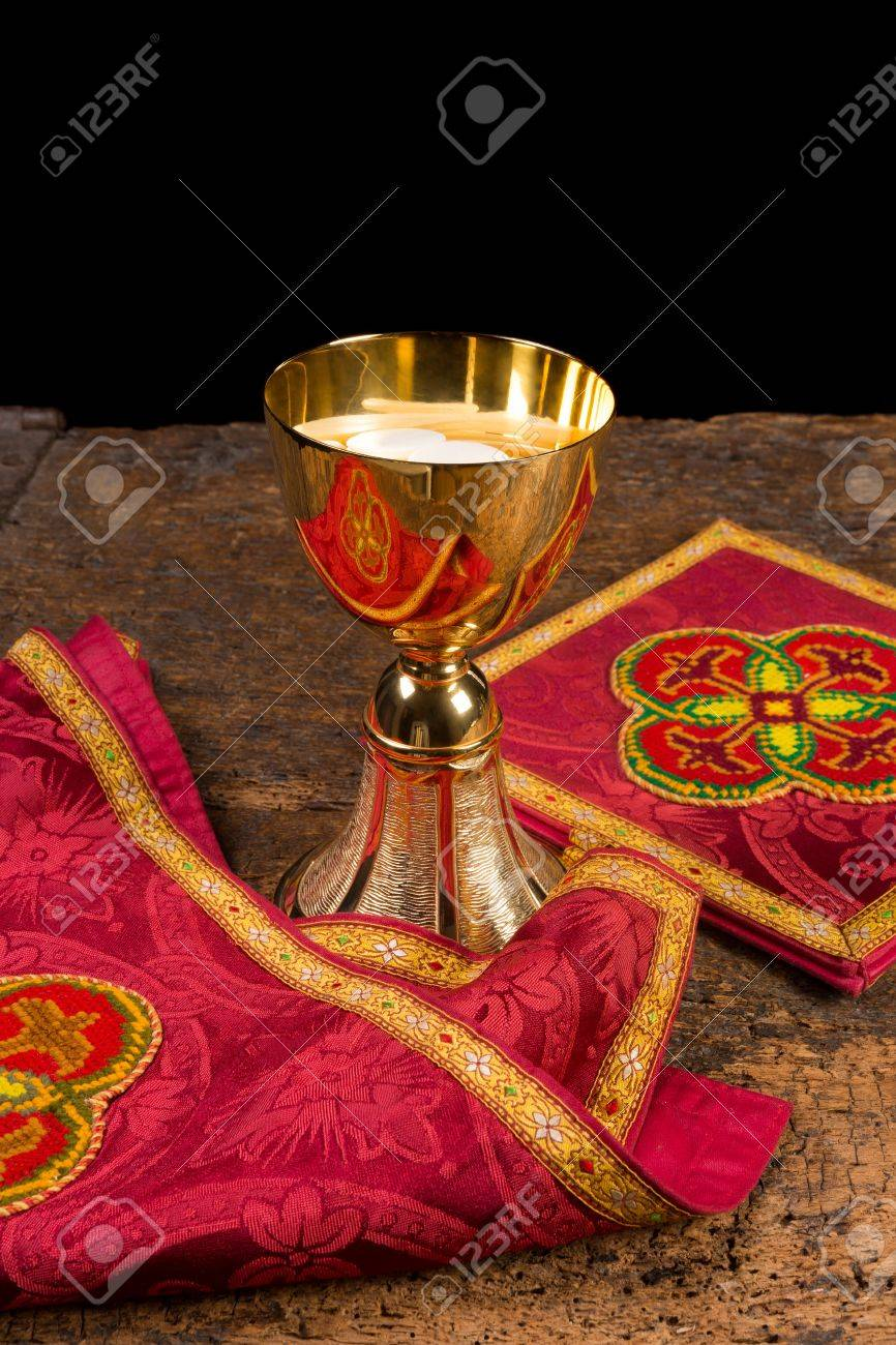 Red damask vestment set of burse and chalice veil, plus chalice filled with holy wafers or hosts Stock Photo - 18676142
