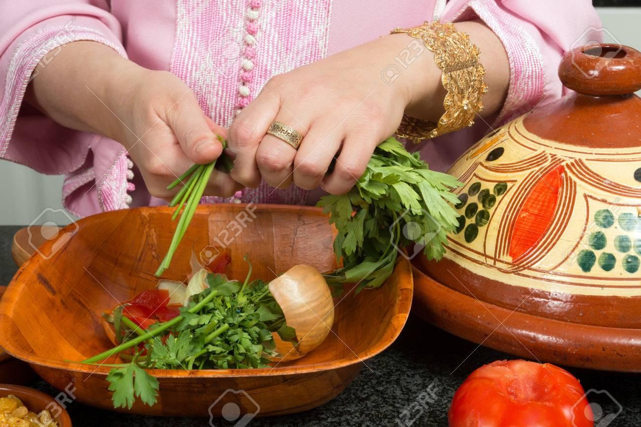 Mains d'une femme en ajoutant les légumes dans un tajine ...