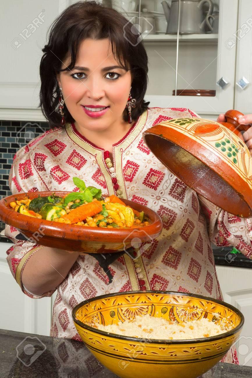 Belle femme marocaine immigrée en europe présentant son plat à ...