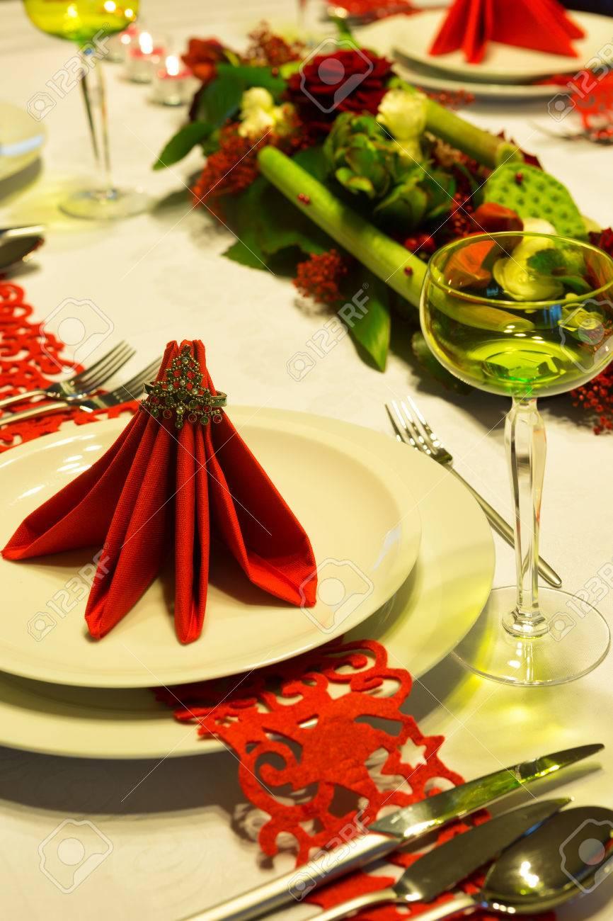 mesa de navidad decorado con servilletas rojas y arreglo de flores foto de archivo