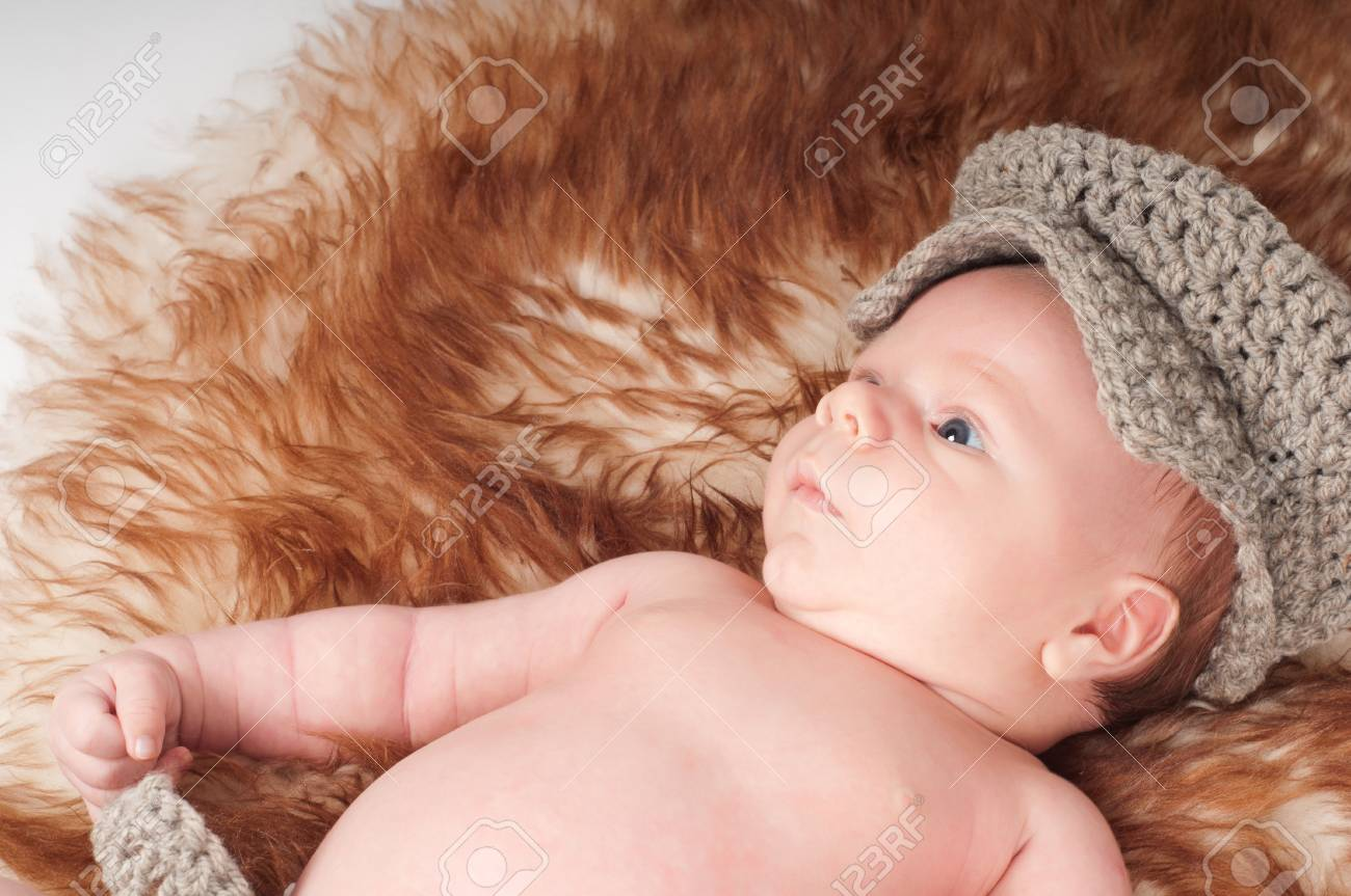 Shot of newborn baby in knitted hat lying on fur Stock Photo - 22607765