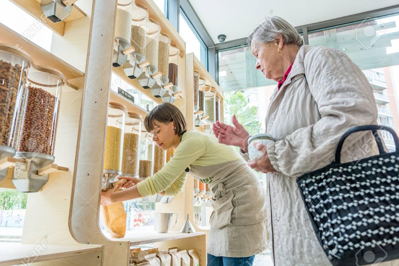 Young female shopkeeper helping elderly lady in zero waste store. - 124692855