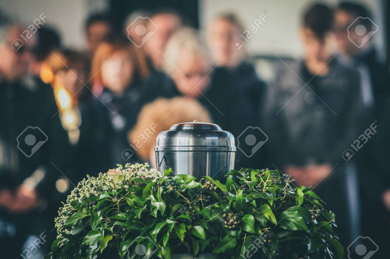 A metal urn with ashes of a dead person on a funeral, with people mourning in the background on a memorial service. Sad grieving moment at the end of a life. Last farewell to a person in an urn. - 148905606