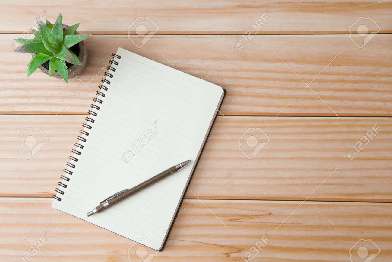 Top view of Notebooks, pens, glasses, cactus on wooden desks with sunlight and copy space - 151401283