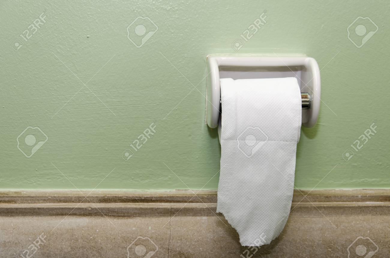 Le papier de toilette accroché au mur de la salle de bains.