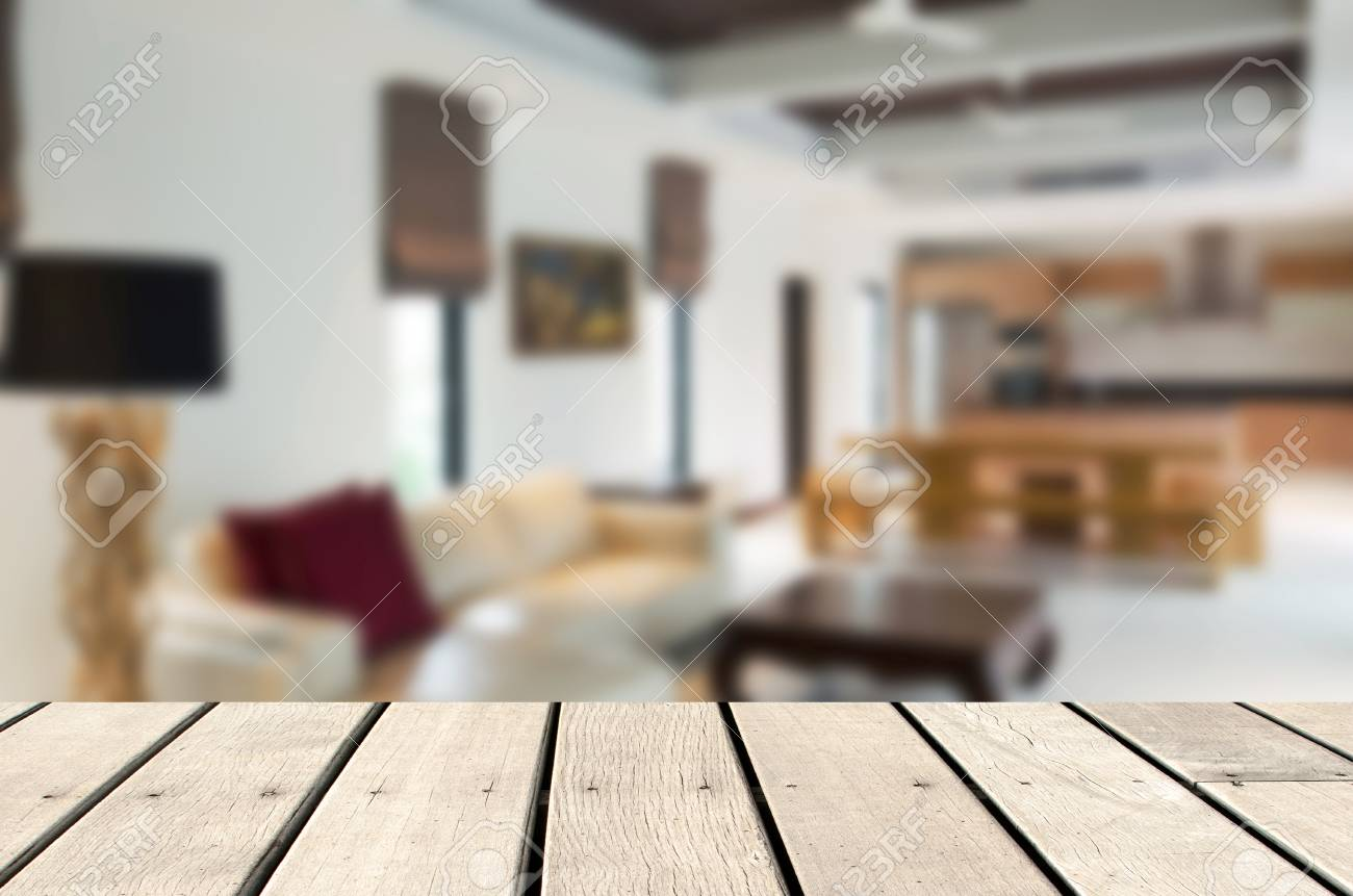 Wood table top blur image of modern living room interior,background..