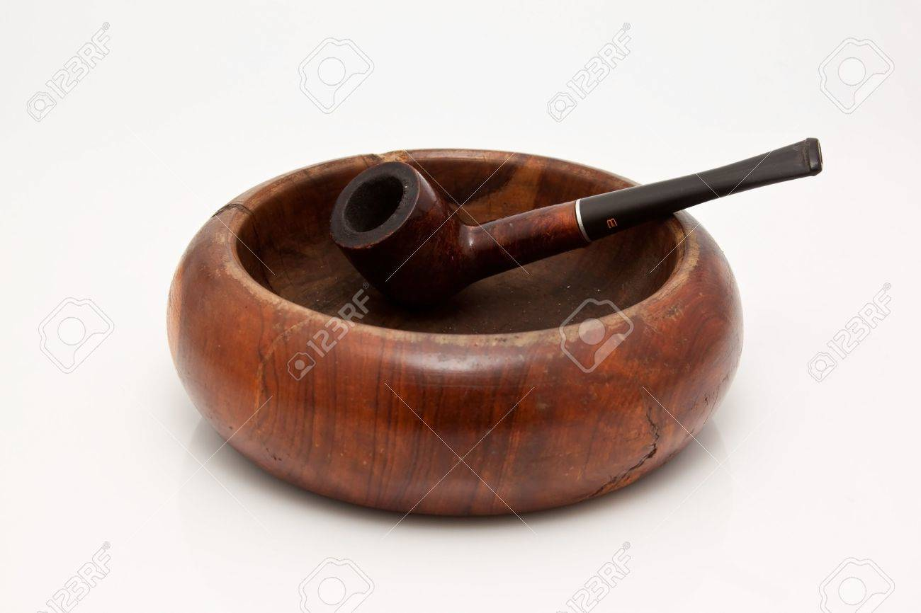 Old wooden pipe in a wooden ashtray Stock Photo - 7688501