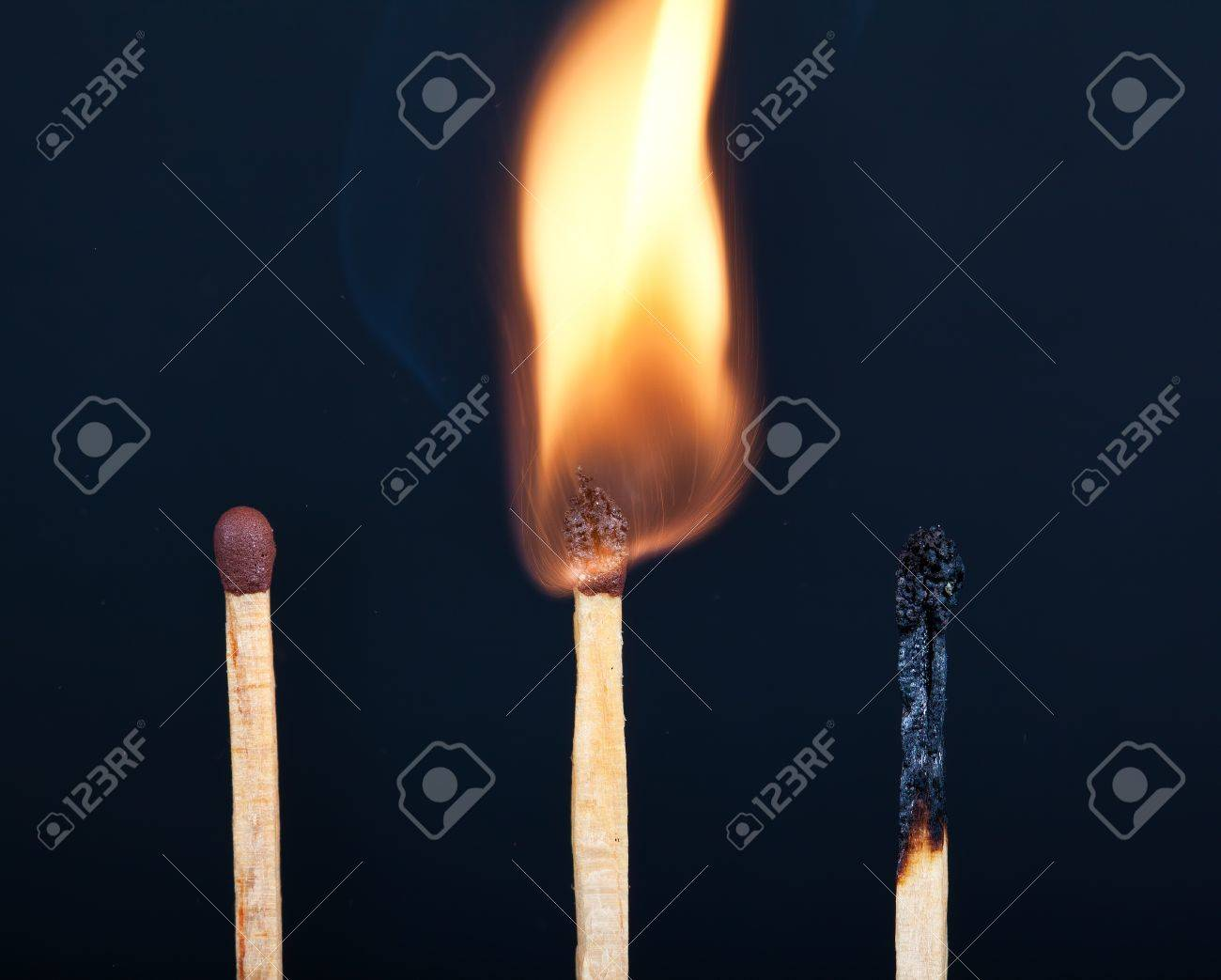 Tree matches in different stages of burning against a black background Stock Photo - 13644896