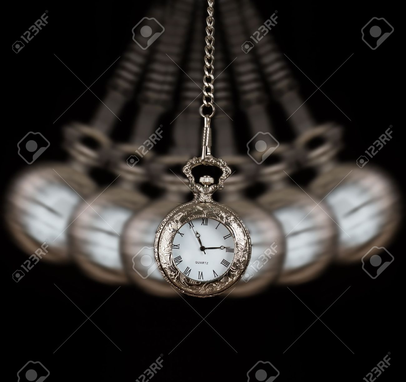 Pocket watch silver swinging on a chain black background to hypnotise Stock Photo - 21710015