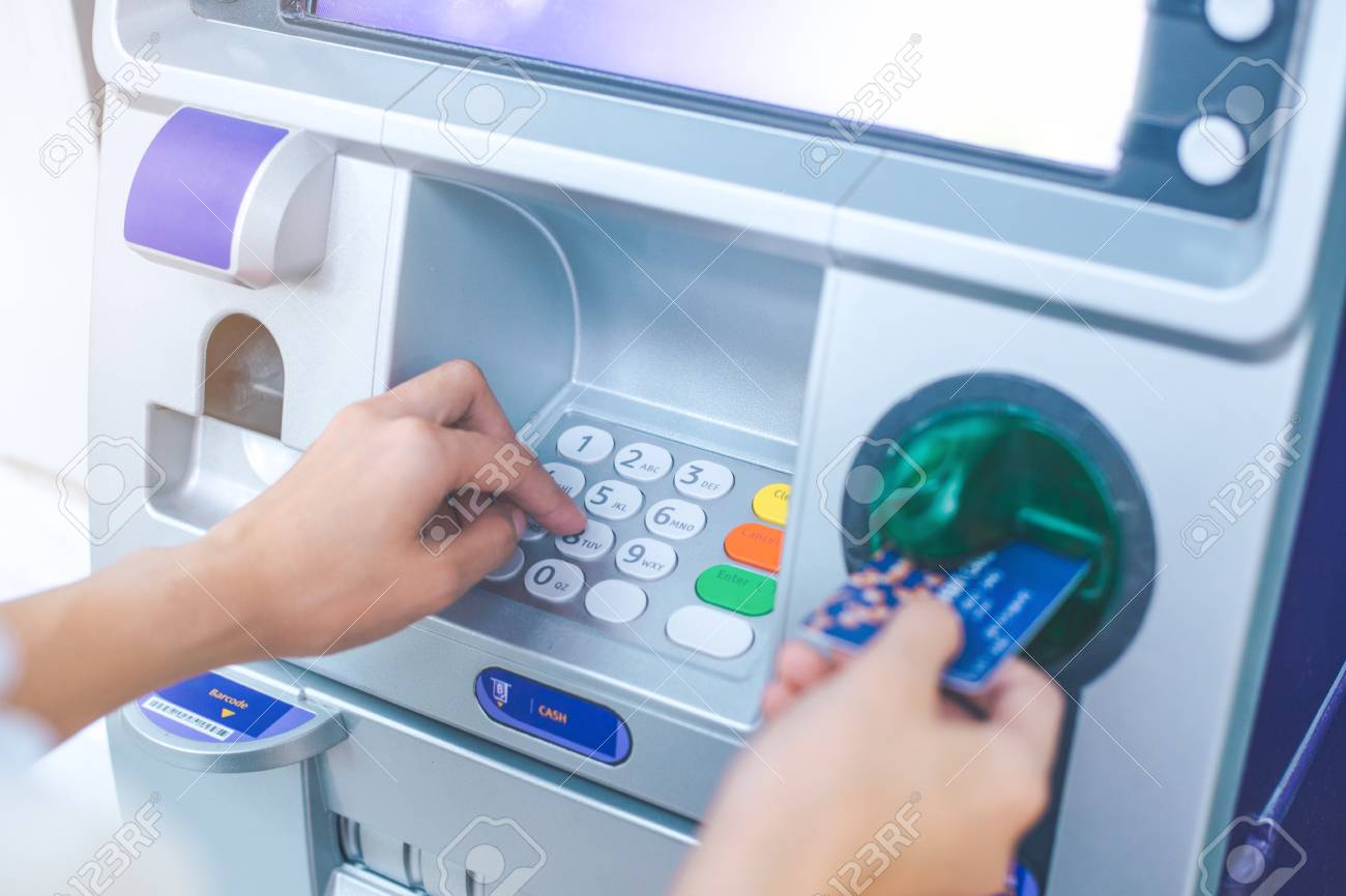 Woman's hand pressing PIN/pass code on ATM/bank machine keypad,And