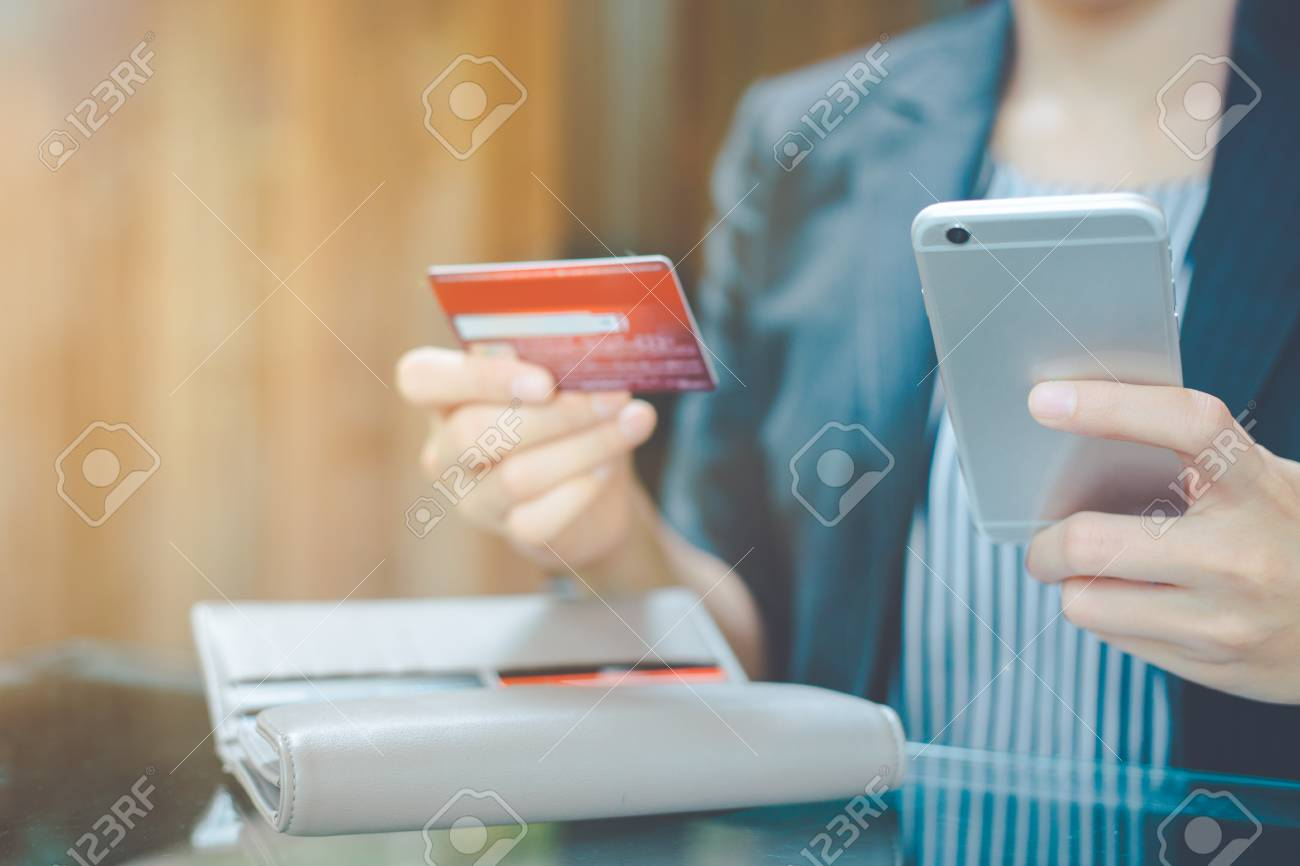 db189403528 Business women hand use mobile phone to shop online through credit cards.  Stock Photo -