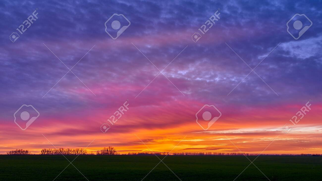 Orange Violet Purple Clouds Over A Green Field Orange Purple Stock Photo Picture And Royalty Free Image Image 135696971