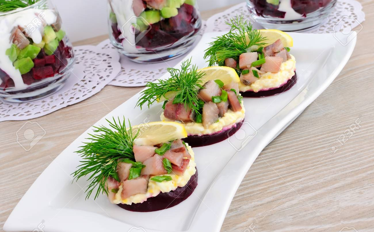 Appetizer of herring with onions on the beets and eggs, lemon and dill Stock Photo - 11880767
