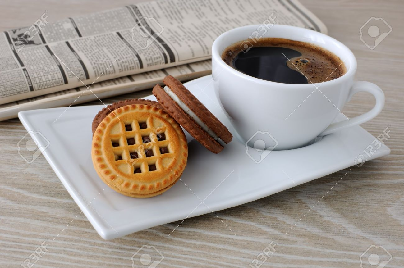 A cup of fresh brewed coffee and biscuits on the table with newspaper Stock Photo - 14993048