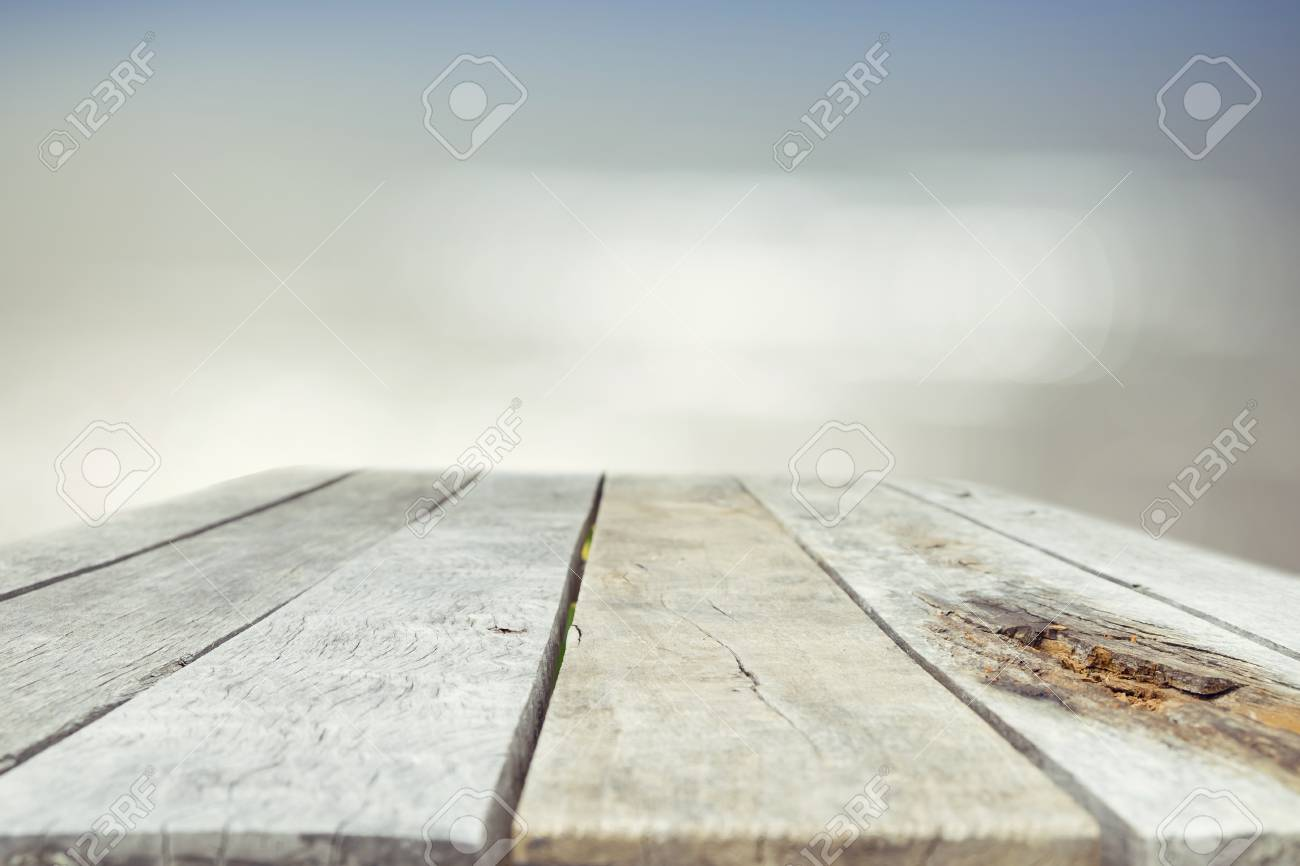 Wood table top on blurred blue sea background - used for display..