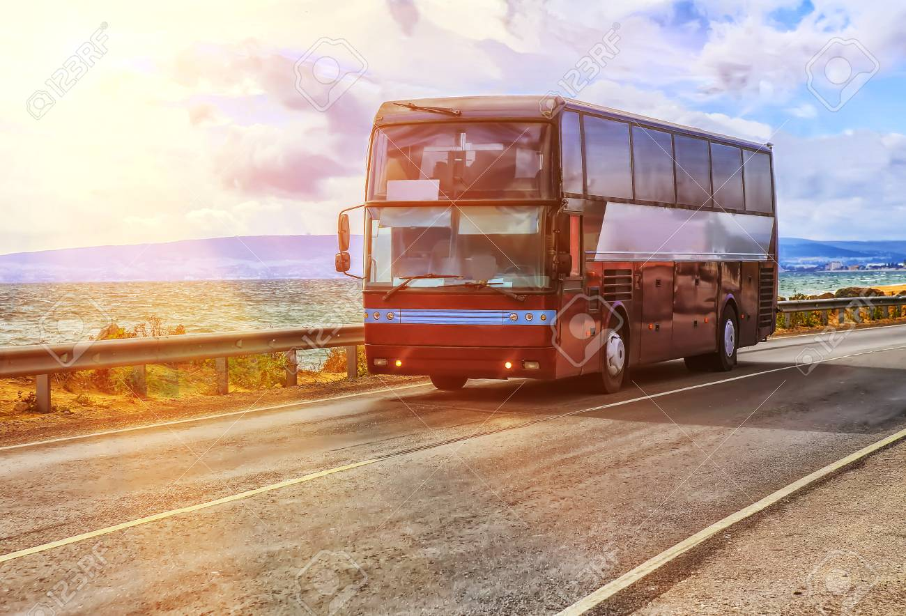 tourist bus is moving along the highway near the sea shore