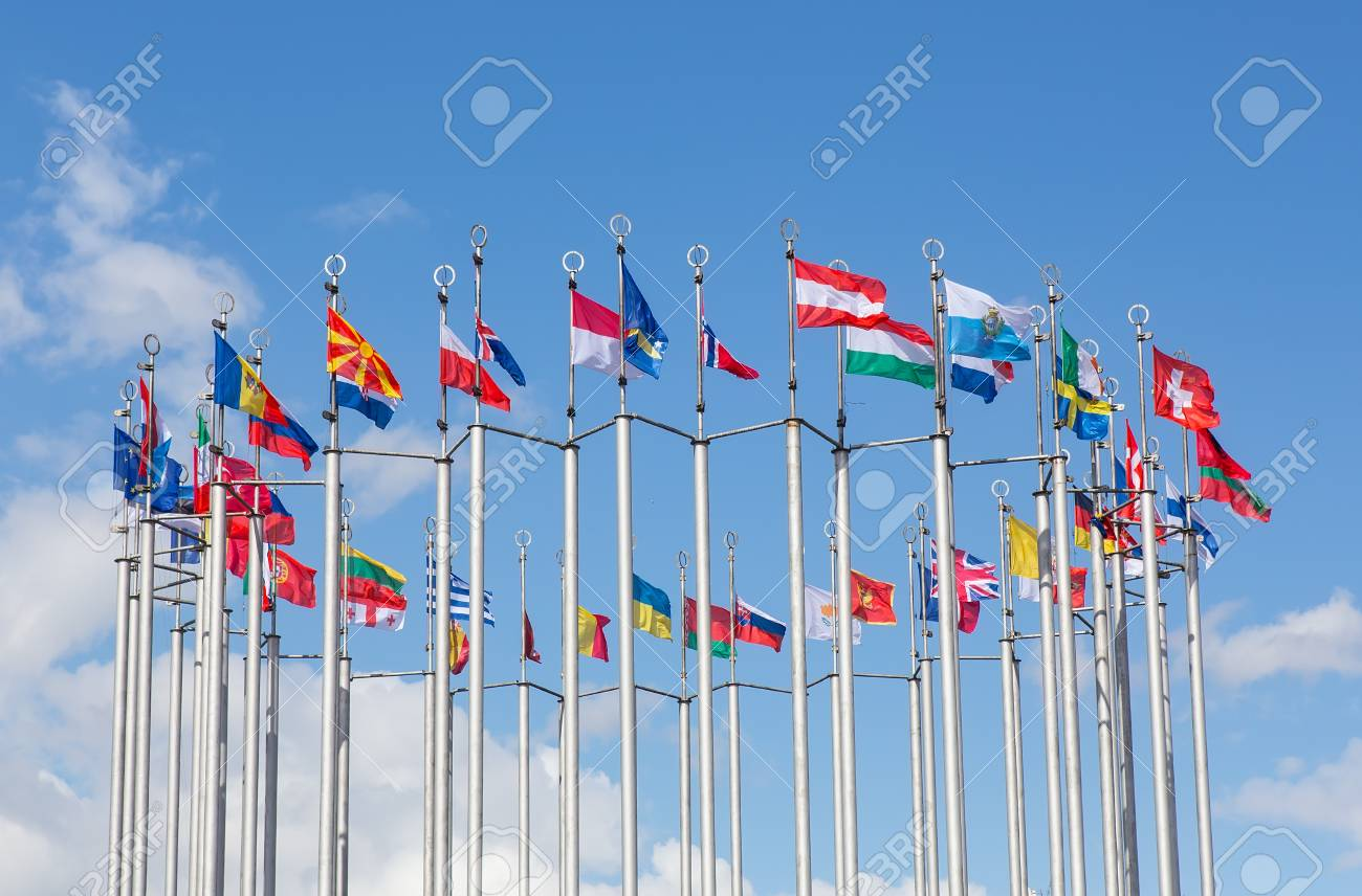 Flags of European states on flagpoles against the background of a cloudy sky. - 102404739