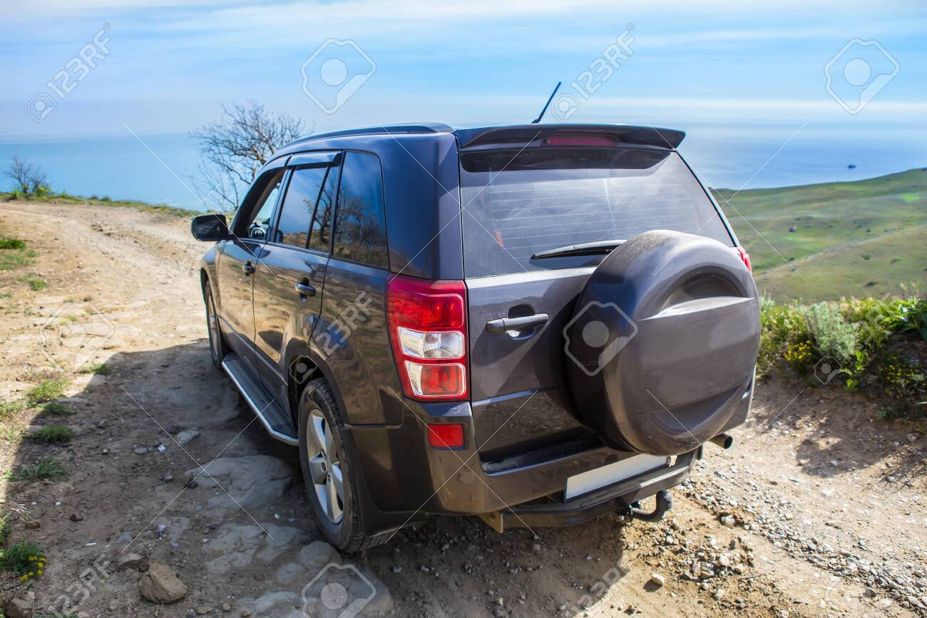 Off-road Car Moves along a dirt mountain road to the sea - 127539386