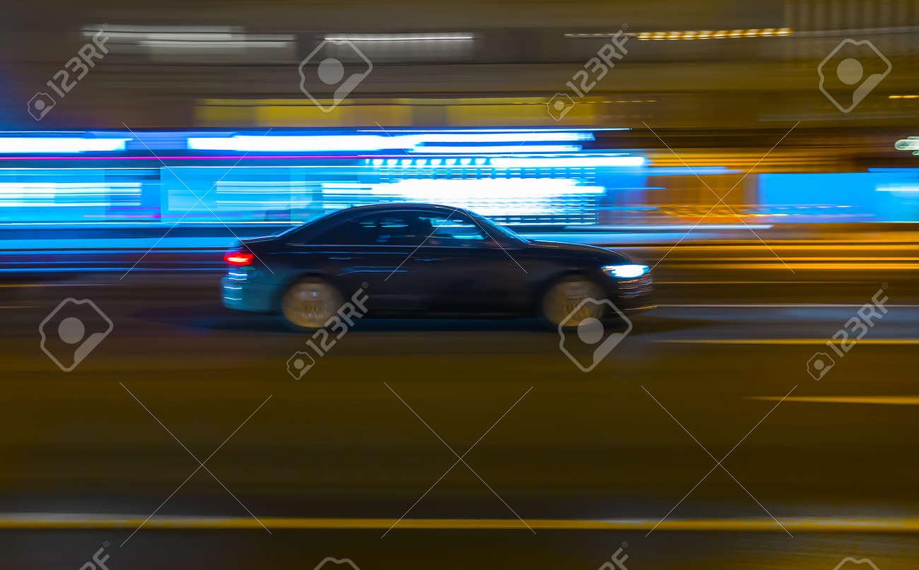 Black car drives along a city street at night. Blurry motion. - 159986239