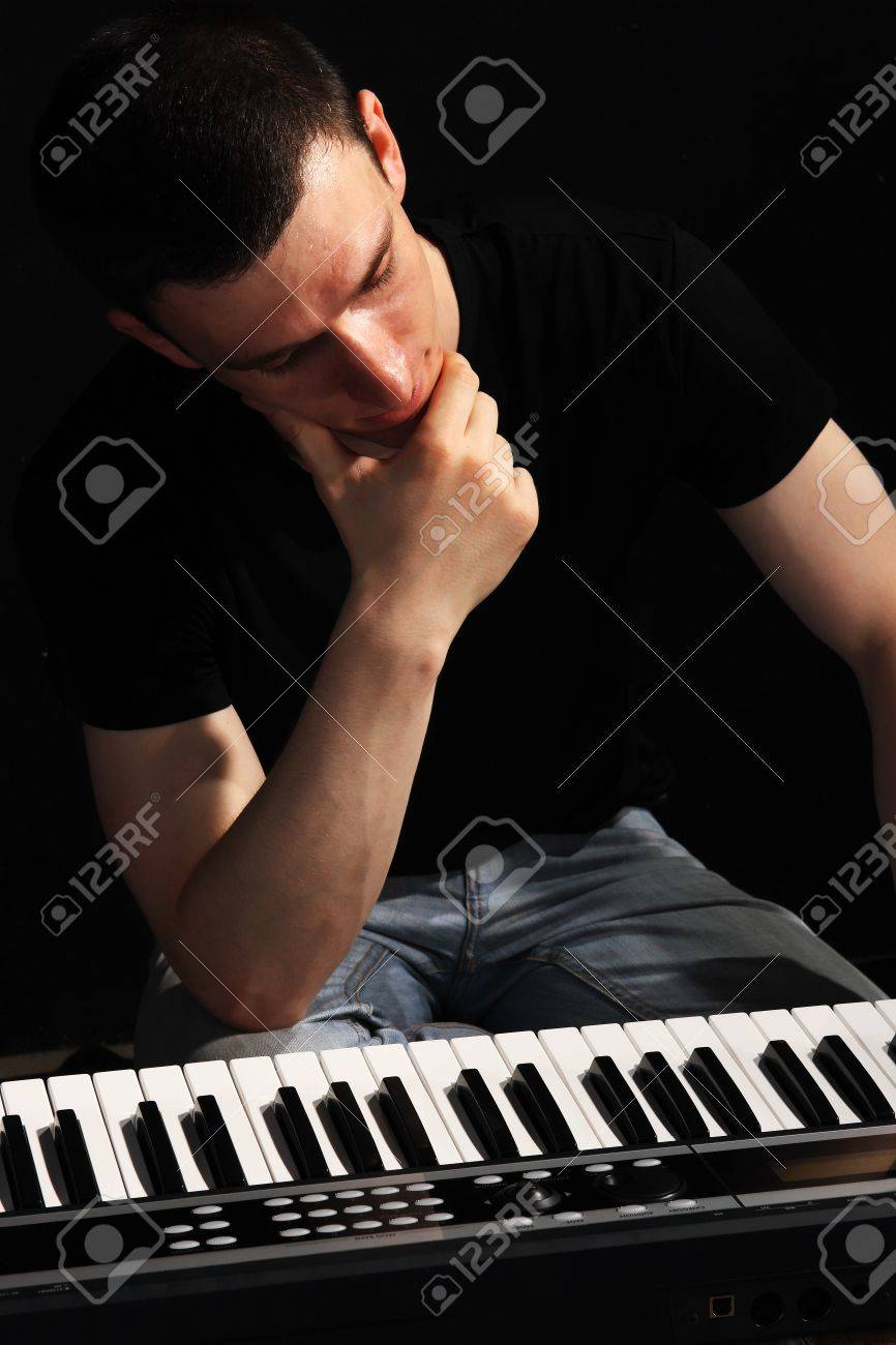 young musician, a pianist on the black background Stock Photo - 7521812