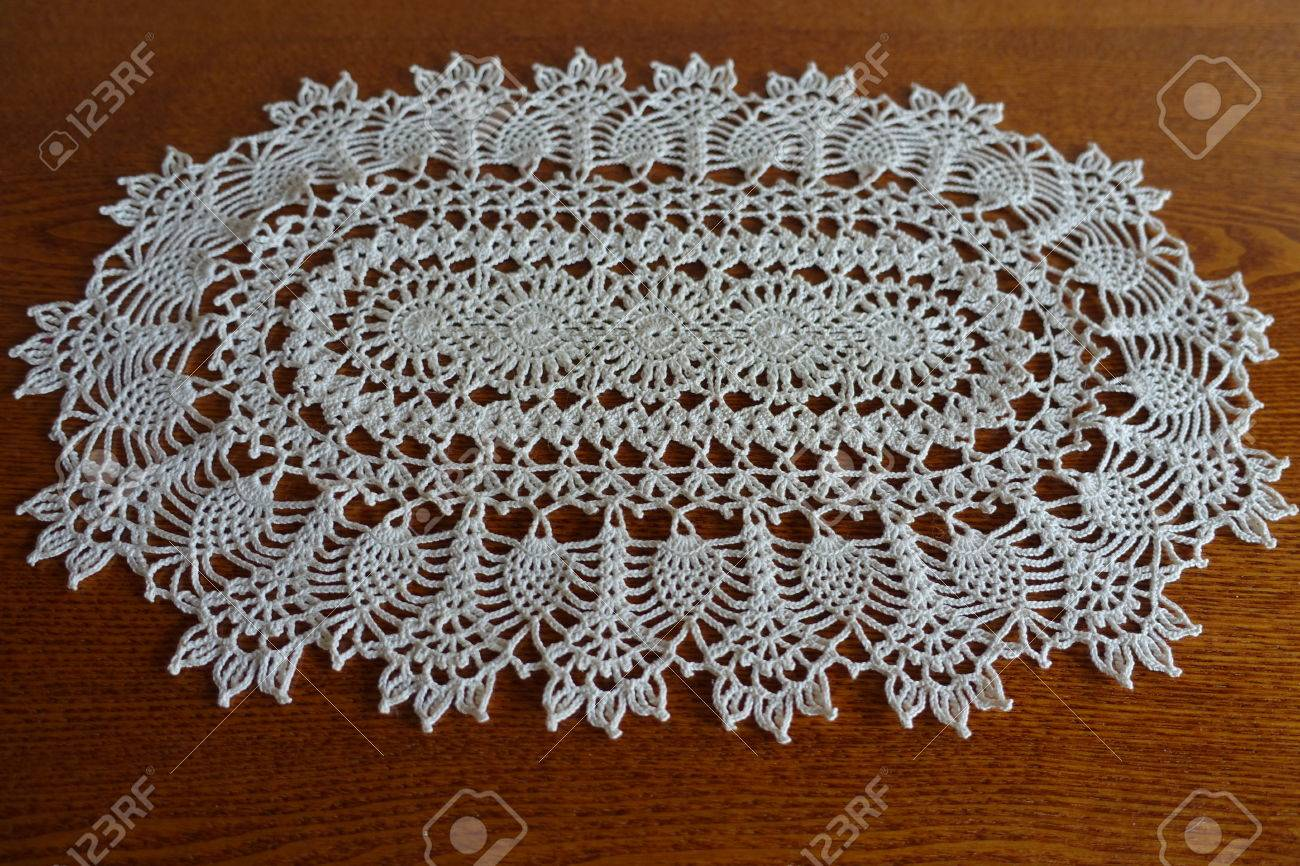 Oval White Handmade Crochet Lace Doily On Wooden Table Stock Photo