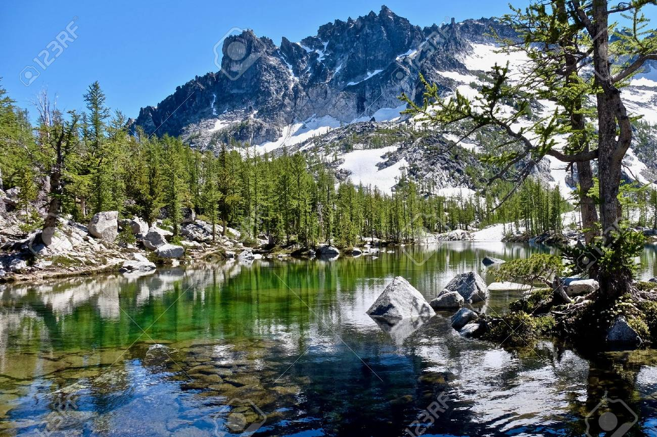 sunlit alpine forest crystal clear lake and granite mountain