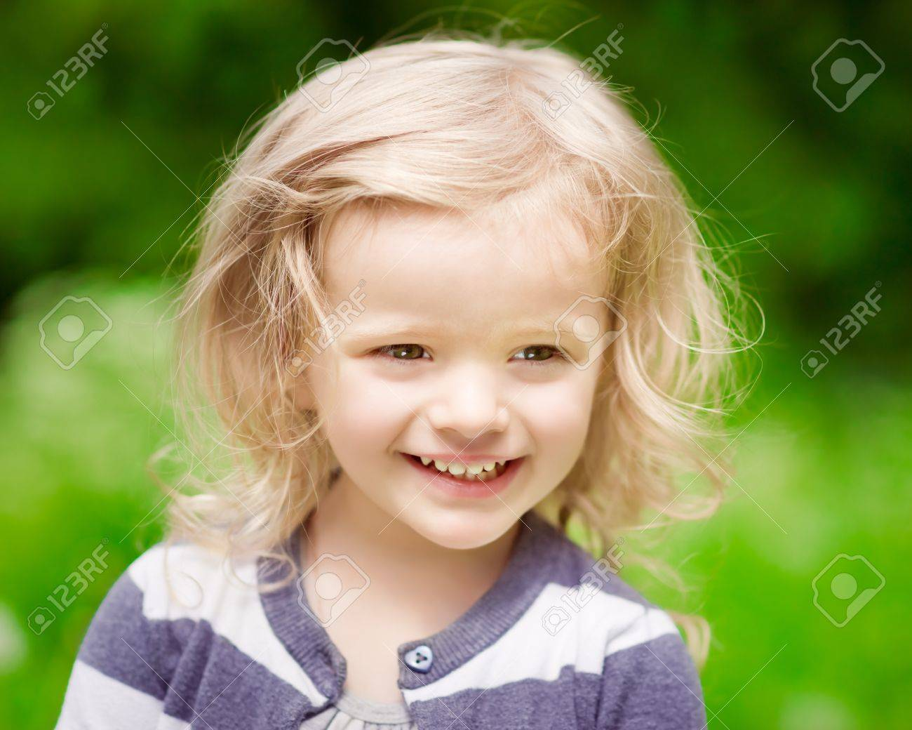 blonde little girl Closeup portrait of a smiling blonde little girl with curly hair in summer  day Stock Photo