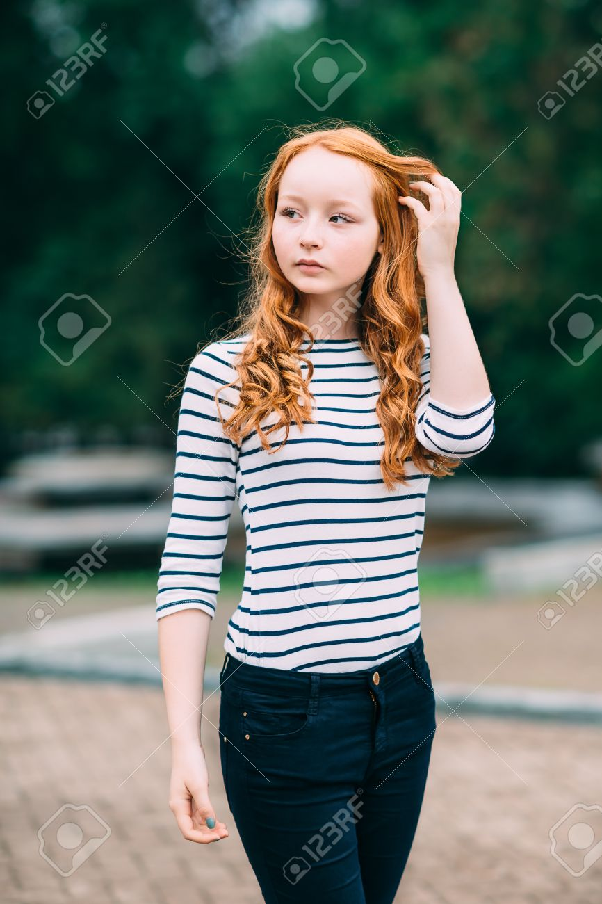016c029a5e ... standing in summer park. Femininity concept. Outdoor portrait of  beautiful girl with long curly red hair and green eyes. Young redhead