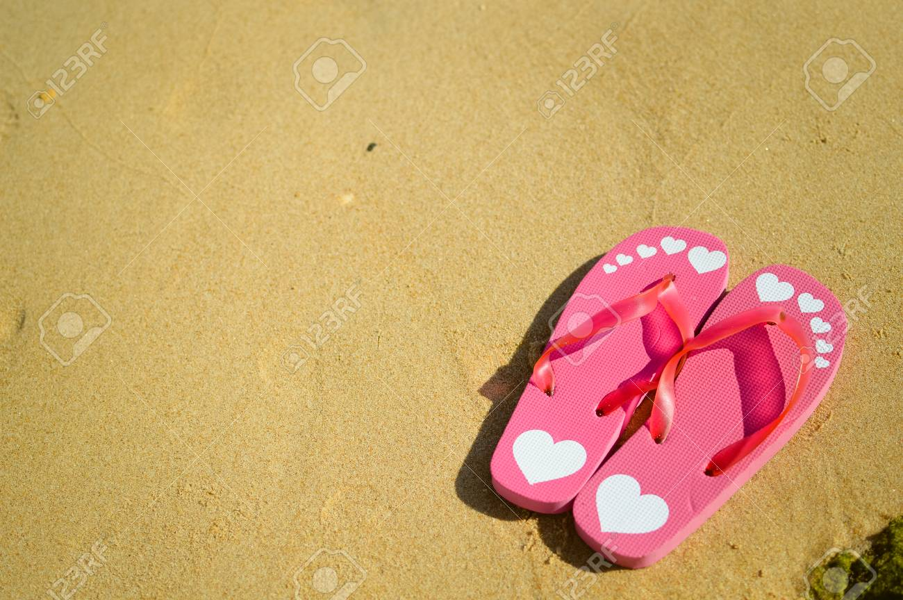 e254bb875 Stock Photo - Top view of flip flops left on a sandy beach background