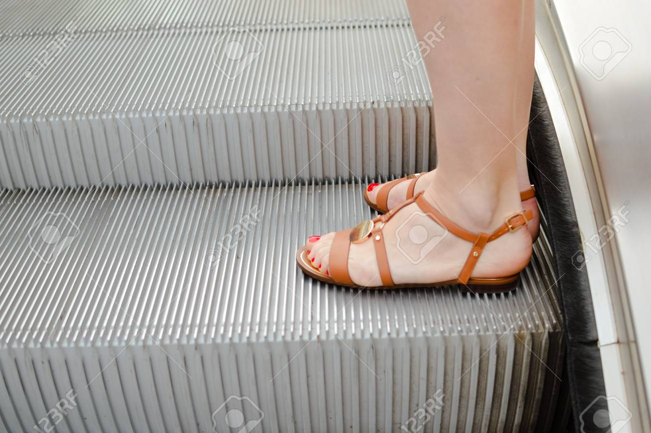 Closeup On Woman Walking On The Escalator Of Shopping Or Office Building  Background. Busy Style