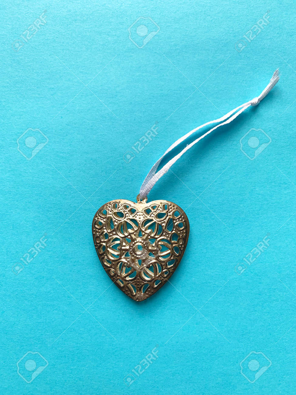 Metal heart pendant on a blue background - 169603111