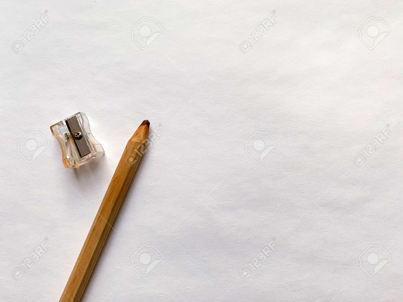 Sharpener and brown pencil on white paper background. - 169603122