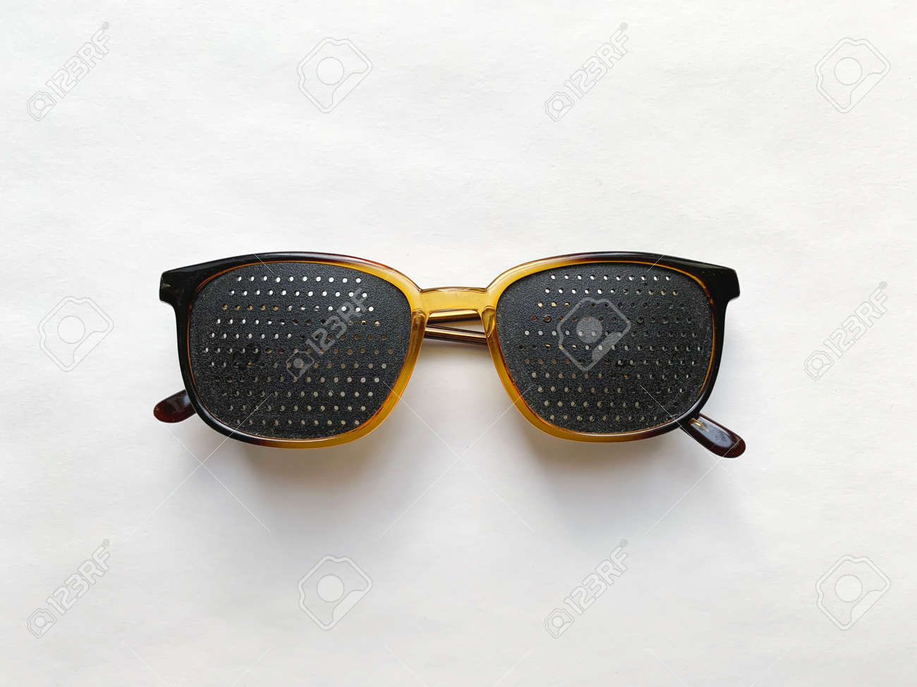 Special perforated glasses for vision correction on a white background. - 169603121