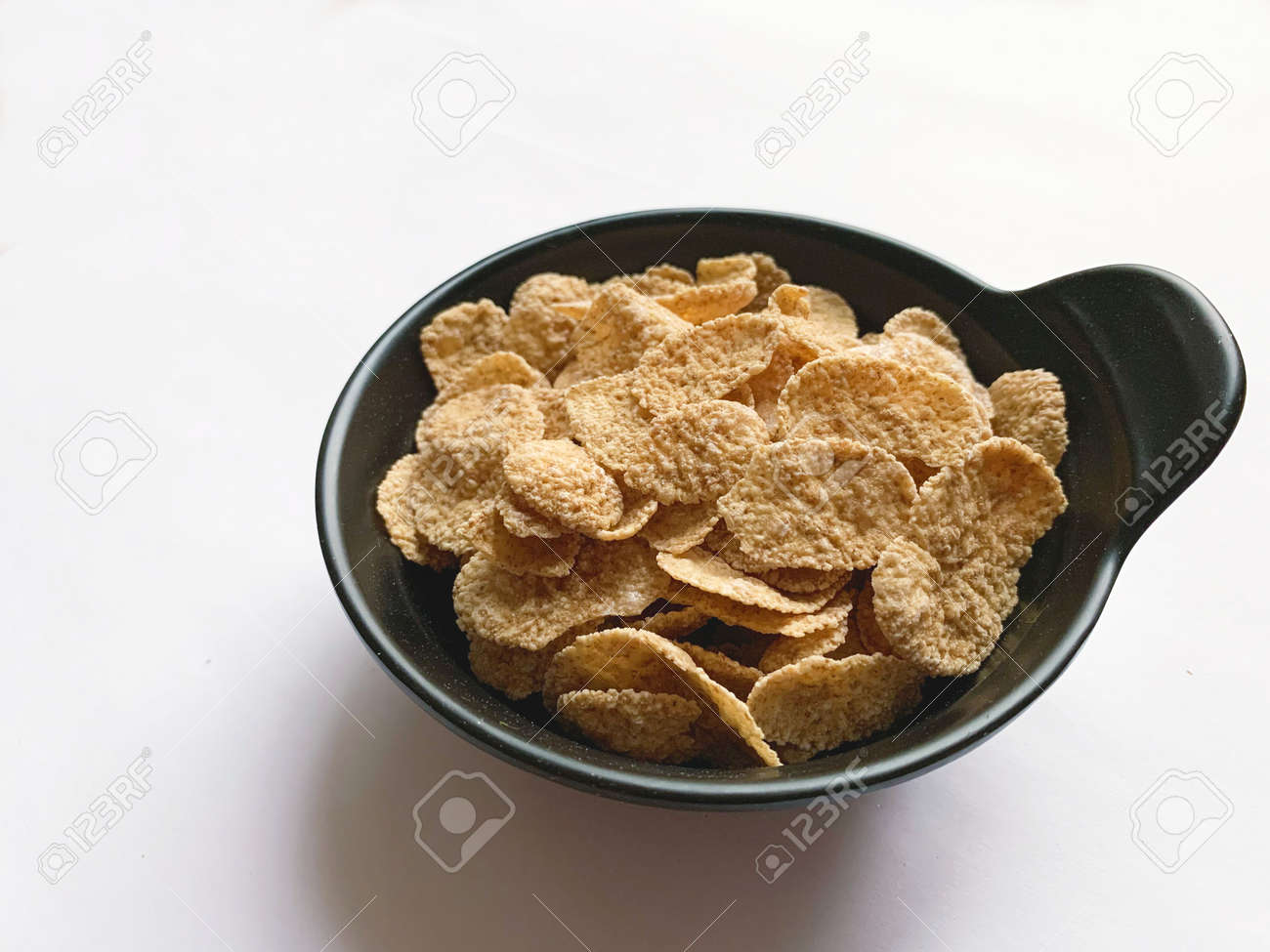 Multi-cereal flakes in a black cup on white background. Closeup. - 169603124